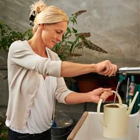 Kvinde der hælder vand i en vandkande