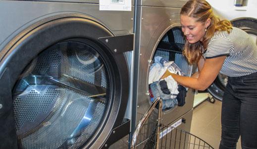 Kvinde putter tøj i gastørretumbler på Rigshospitalets Kollegium