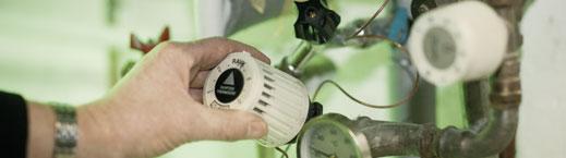 Billede af en termostat, der bliver justeret