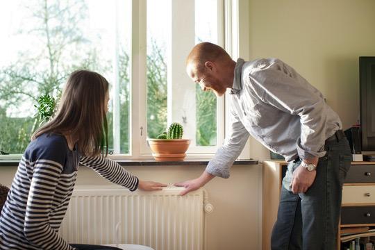 Billede af personer, der mærker varmen på radiator