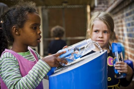 børn der fylder deres vandflasker med drikkevand fra vandpost