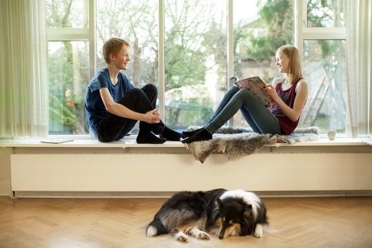 Pige og dreng sidder i vindueskarm over radiator, som leder fjernvarme ud i hjemmet